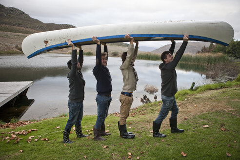 Four friends carrying a canoe in front of a lake - ZEF005807