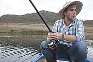 Fishing young man sitting in a canoe on a lake - ZEF005794