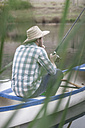 Fishing man sitting in a canoe on a lake - ZEF005804