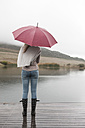 Back view of young woman standing in the rain with umbrella - ZEF006225