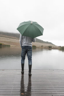 Man standing in the rain on wooden boardwalk with green umbrella - ZEF006227
