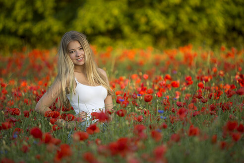 Germany, Bavaria, portrait of girl in a poppy field - YRF000083