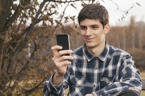 Portrait of smiling young man using his smartphone in a park - BZF000161