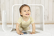 Portrait of smiling baby girl crouching under modern side table - DRF001650