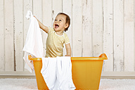 Baby girl standing in a laundry basket - DRF001652