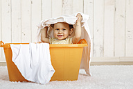 Baby girl sitting in a laundry basket - DRF001653