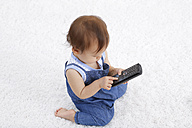 Baby girl playing with cordless telephone - DRF001658