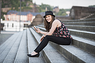 Germany, Koblenz, Deutsches Eck, young woman with cell phone sitting on stairs - PAF001429