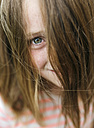 Portrait of smiling girl peeking through her hair - MGOF000275