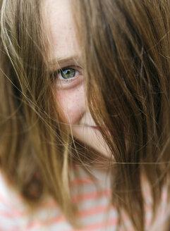 Portrait of smiling girl peeking through her hair - MGOF000275