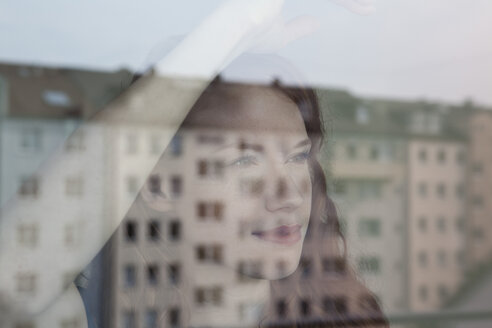 Young woman looking out of window - RBF002773
