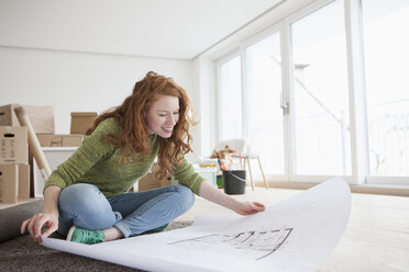 Young woman in new flat with cardboard boxes looking at ground plan - RBF002776