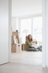 Young woman in new flat with cardboard boxes looking at ground plan - RBF002857