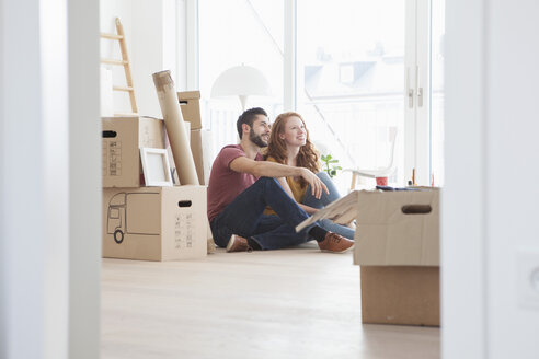 Young couple in new flat with cardboard boxes - RBF002862
