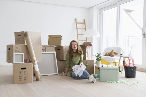 Young woman in new flat with cardboard boxes holding ground plan - RBF002870