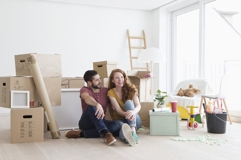Young couple in new flat with cardboard boxes, sitting on floor - RBF002867