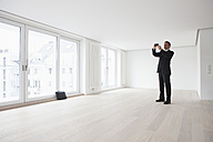 Estate agent standing in empty apartement, taking pictures - RBF002798
