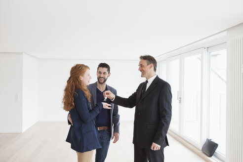 Estate agent handing over keys to young couple - RBF002806