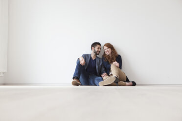 Young couple sitting on floor of their new flat - RBF002812