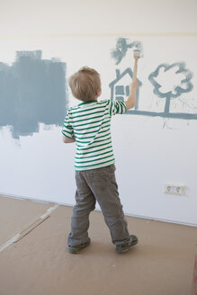Little boy painting house and tree on wall of his new room - RBF002825