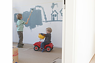 Little boy painting house and tree on wall of his new room - RBF002828