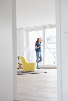 Young woman standing in her living room looking through window - RBF002757