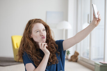 Young woman sitting in her living room taking a selfie with smartphone - RBF002763