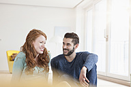 Young couple sitting on the floor of living room - RBF002834