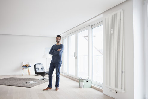 Young man with crossed arms standing in his living room - RBF002841
