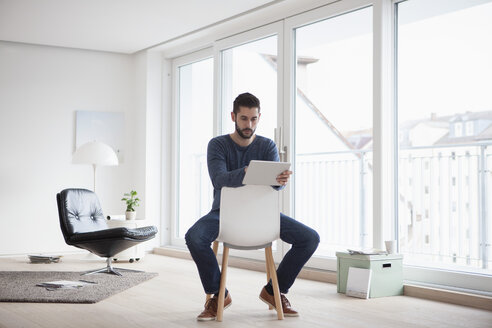 Young man sitting on chair in his living room using digital tablet - RBF002844