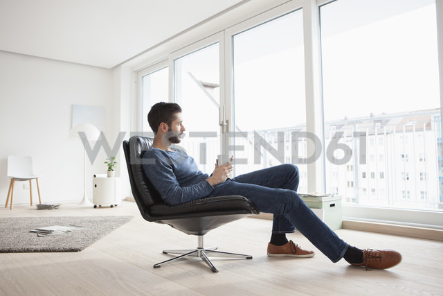 Young man relaxing on leather chair with cup of coffee in his living room - RBF002847
