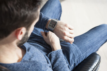 Young man sitting on leather chair looking at his smartwatch - RBF002767