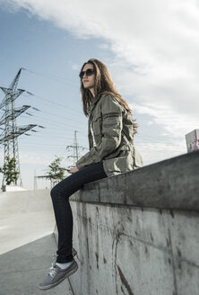 Young woman wearing sunglasses sitting on a wall with smartphone - UUF004587