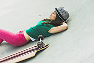 Young woman lying besides her skateboard having a rest - UUF004609