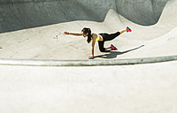 Young woman doing stretching exercises in a skate park - UUF004663