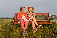 Greece, Corfu, Afionas, two little girls sitting side by side on a bench at evening twilight - JFEF000683