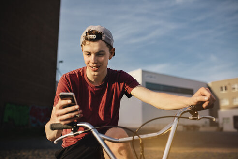 Young man with BMX bicycle looking on cell phone - GCF000088