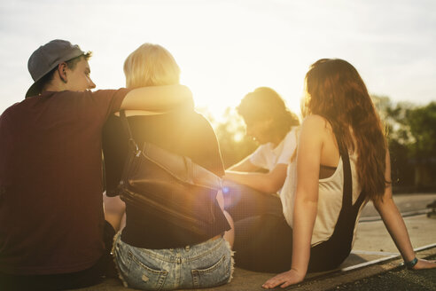 Friends sitting together outdoors at sunset - GCF000118
