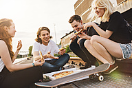 Friends sitting together outdoors sharing a pizza - GCF000100