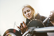 Young woman repairing BMX bicycle - GCF000101