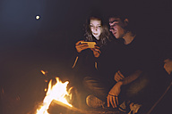 Young couple sitting together at the campfire looking at cell phone - GCF000124