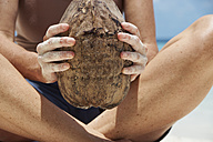 Maldives, close-up of woman holding coconut - STKF001284