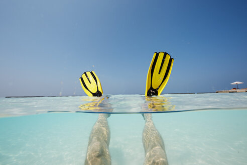 Maldives, man's feet with flippers in shallow water - STKF001289