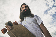Low angle view of a hipster type man with a longboard - SELF000061