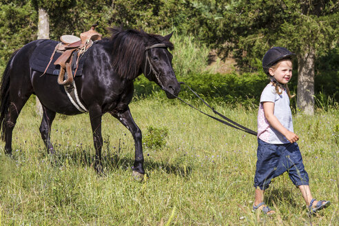 Greece, Corfu, Agios Georgios, little girl leading horse on a meadow - JFEF000687