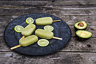 Plate of avocado ice lollies and slices of lime - SARF001872