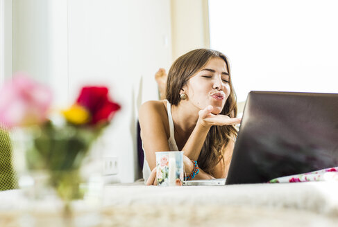Relaxed young woman lying in bed using laptop blowing a kiss - UUF004678