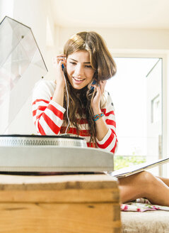 Young woman at home with headphones and record player - UUF004685