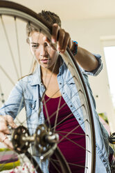 Young woman at home repairing her bicycle - UUF004694