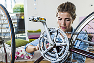 Young woman at home repairing her bicycle - UUF004695